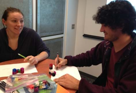 A photograph shows two teens at a table drawing two-dimensional illustrations on paper of the three-dimensional cubes on the table in front of them.