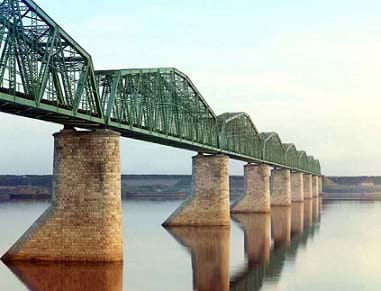 A photo shows a steel truss railroad bridge supported by eight brick pillars spans a still body of water. The truss design uses repeated triangular shapes composed of steel beams.