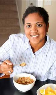 A photograph shows a woman at a table taking a bite of cereal from a bowl.