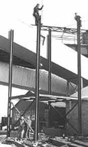 A black and white photo shows a tall I-beam structure with two men up high, working on the beams.