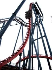 A photo of a roller coaster shows a car coming down the first big hill.