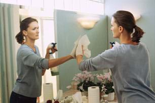 Photo shows a woman using paper towels and a spray bottle of liquid to clean a wall mirror.