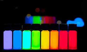 A photograph in a dark room shows a lineup of eight vivid and glowing bottles of quantum dots composing the ROYGBIV color spectrum from violet to deep red.