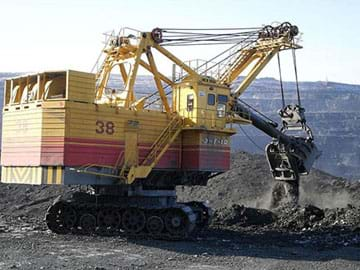A photograph shows heavy equipment—an excavator—mining dark soil with its digger attachment.