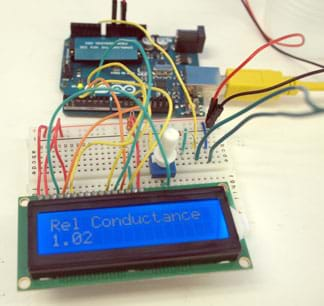 A photograph shows a microcontroller board connected by wires to a breadboard with many colored wires and some circuitry components as well as a LCD display that reads: Rel Conductance 1.02.