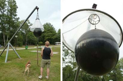 Two images show a metal tripod supporting an angular pole from which hangs about 4 meters from the ground a large, white cone (pointed side up) around a large black ball that hangs partially below the cone.