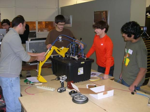 Photo shows four students at a table using PFPDs.