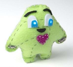 """A photograph shows a plump, blob-shaped """"plush"""" toy creature with loosely shaped arms and legs, light-up cartoon eyes (from sewn-in circuit with LEDs), eyebrows and a red heart made of stitched green felt."""