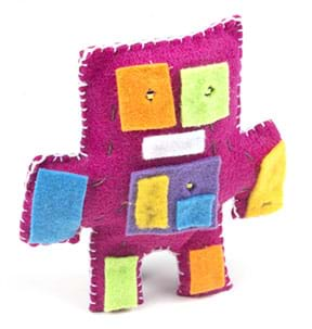 A photograph shows a light-up plush toy made of pink felt with white edge stitching that is shaped with squared off head, arms and legs, and squares of different felt colors added for eyes, hands and feet, as well as to cover the battery holder in the center.