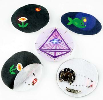 A photograph shows three completed light-up pins (flower and sun, fish, pyramid with eye). The flower pin is also flipped over to show its battery pack on the back that provides an electricity source, and a pin to attach it to clothing. Another photo of the same pin shows its front fabric layer pulled back to reveal its middle layer with a sewn-in inner circuit and LED light on felt.