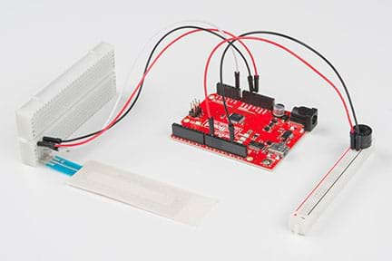 A photograph shows the activity setup. On the left, a potentiometer is plugged into the larger part of a cut breadboard with three wires (red, black and white) leading to the RedBoard (center). Two different wires (red and black, respectively) connected to the RedBoard then lead to a speaker plugged into the smaller, cut-off portion of the breadboard (located on the right).