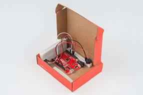 A photograph shows a lidded cardboard box containing the breadboard with the speaker, the RedBoard, and the breadboard with the potentiometer, all connected with wires.