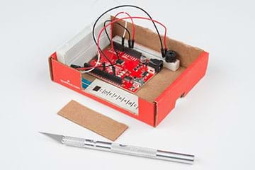 A photograph shows a cardboard box containing a RedBoard, breadboard with speaker, a breadboard with potentiometer, and notches on the front and right box sides to permit keyboard and power cord access.