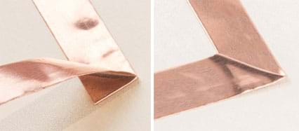 Two photographs: A strip of copper tape is adhered to paper and then at some point it is bent backwards on itself (before being adhered) and then turned at a right angle. Then after folding down to make a square corner (the turn), the copper tape continues being placed in a line on the paper.