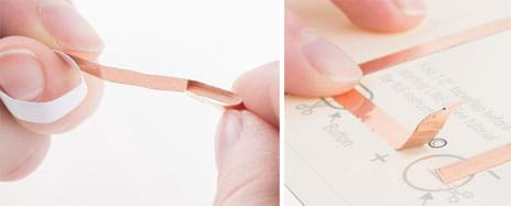 Two photographs. One hand holds the end of a strip of copper tape while another hand's fingers bend back about a half-inch of the end of the tape so it sticks to itself. This is done at a location on a paper circuit so that the flap of copper tape is positioned over a circle on the template diagram, which represents the coil cell battery location.