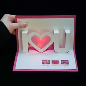 """A photograph shows a hand opening a red and white pop-up and light-up valentine card that says """"I <heart> you."""""""