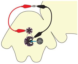 A diagram like Figure 3 with the addition of two alligator clips and an LED to show a test circuit. A black alligator clip runs from the negative pin on the battery holder to the negative pin of the LED. A red alligator clip attaches the positive pin of the LED to one of the numbered LilytTiny sequence pins.