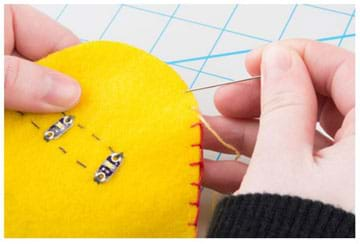 A photograph shows a hand holding a felt monster cutout with its sewn circuitry visible and another hand using a needle with colored embroidery thread to stitch up the outer seam, which joins the two sides together in order to close it up for stuffing.