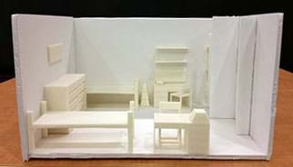 """A photograph shows a diorama-type scale model of a dorm room that looks like a box with the top and one long rectangular sides open. Inside the """"box"""" is assorted 3D-printed furniture along the walls (two beds, two desks, two chairs, two dressers, two bookshelves, and a few other organizational items) arranged in an open floor plan."""