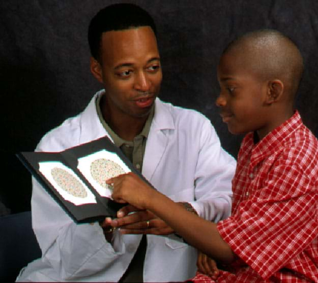 A photograph shows a man in a white coat sitting next to a young boy in a dark room. The doctor holds two color plates and waits for the child to tell him what he sees.