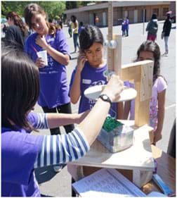 A photograph shows young students watching a teacher measure an egg catcher (looks like a box filled with shredded paper) by using a homemade wooden tool that consists of a 25-cm wood circle and a sliding ruler. A student team hopes its egg catcher is not too big!