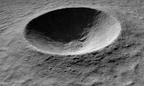 A black and white photograph shows a round concave indentation in a slightly textured surface.