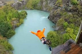 A person in an orange jacket, with a bungee cord attached to his ankles jumps off a platform headfirst into a gorge with a river at its base.