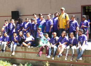 A photograph shows a group of 20+ students in matching purple T-shirts posed in a group outside a school on an award stage; they are competition participants from the winning school.