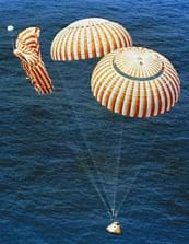 A photograph shows the Apollo 14 capsule descending into the ocean for splashdown with two of its three red and white stripped parachutes fully inflated.