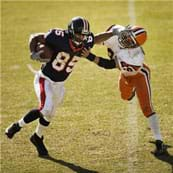 A photograph shows a football player with the ball giving a stiff-arm to another football player attacking him.