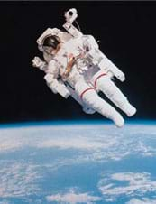 A photograph shows an astronaut in a puffy white suit and glass-faced helmet floating in space with the Earth in the distant background.