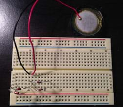 The same breadboard as Figure 2, now with a two-wire piezo element connected with black and red wires