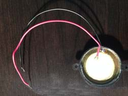 A photograph shows a white ceramic disc with larger gold metal disc underneath it. A red wire is soldered to the white part and a black wire to the gold part.
