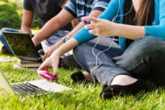 A photograph shows three teenagers sitting on the grass using laptops and cell phones and listening to music with ear buds.