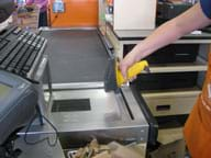 Photo shows a person using a handheld barcode scanner at a store check-out stand.