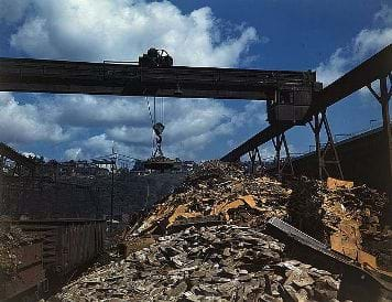 A photograph shows carloads of scrap metal being sorted and moved at the Allegheny Ludlum Steel Corp.'s steel mill in Pennsylvania in the 1940s. An overhead magnet deposits the scrap in a loader that carries it to a furnace to be melted down for re-use.
