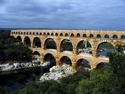 The Pont du Gard, a double high, multi-arched long structure—an ancient aqueduct.