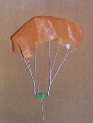 Photo shows a parachute made with a paper canopy, six taped strings and a weight.