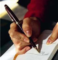 Photograph shows a hand holding an ink pen and writing on paper.