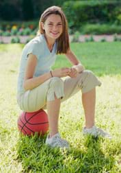 A photograph shows a girl wearing sneakers sitting on a basketball.