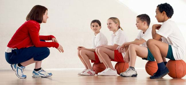 A photograph shows a female coach talking to four kids with basketballs who are all wearing various kinds of sneakers.