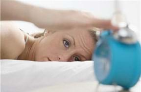 Photograph shows a woman waking up and reaching for an alarm clock near her bed.